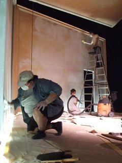 Scenic Painter Leah McDermott and assistant Zinnia sanding and plastering the walls